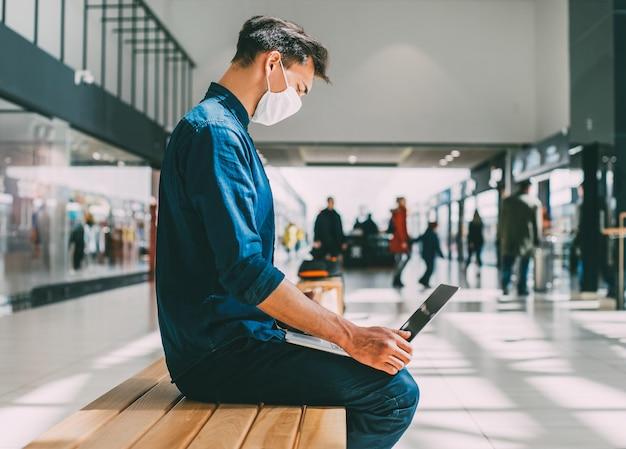 Mężczyzna w masce ochronnej pracuje na laptopie w pobliżu budynku miasta. pandemia w mieście