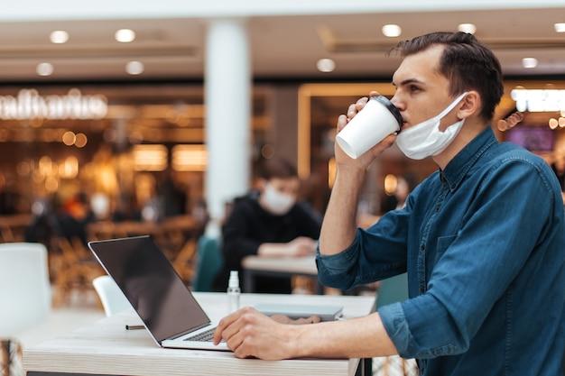 Mężczyzna w masce ochronnej siedzi przy stoliku w kawiarni. zdjęcie z przestrzenią do kopiowania