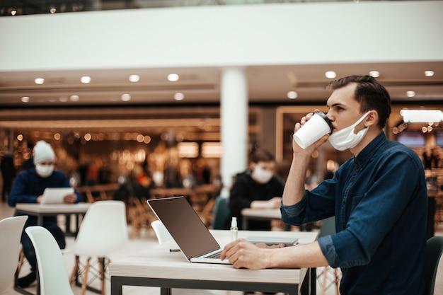 Mężczyzna w masce ochronnej siedzi przy stoliku w kawiarni.
