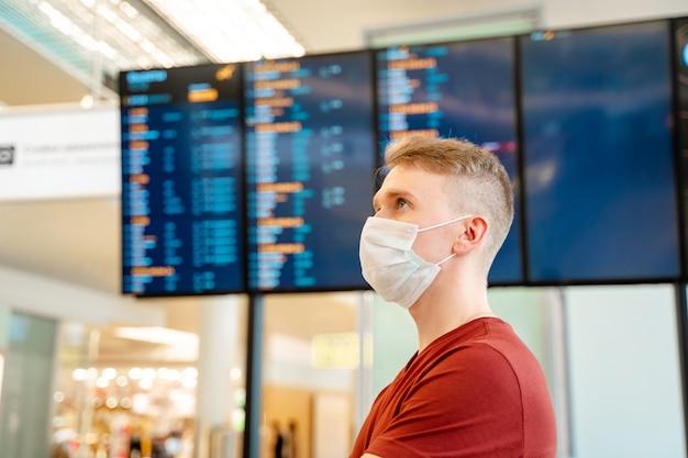 Mężczyzna w masce ochronnej stoi na lotnisku w tablicy odlotów i przylotów