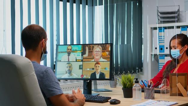 Mężczyzna w masce ochronnej uczestniczący w wideokonferencji grupowej online w nowym, normalnym biurze. freelancer pracujący w miejscu pracy, rozmawiający, rozmawiający podczas wirtualnego spotkania, wykorzystujący technologię internetową