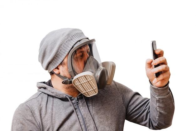 Mężczyzna w masce oddechowej o podwyższonym stopniu ochrony przed szkodliwymi czynnikami środowiskowymi. pełna maska na twarz. mężczyzna używa swojego smartfona.