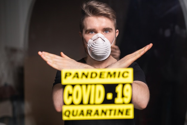 Mężczyzna w masce oddechowej pokazujący gest stop. facet pokaż gest nr. powstrzymaj koronawirusa lub covid-19 i pandemię