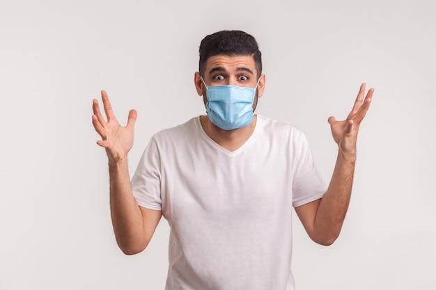 Mężczyzna w masce podnoszący ręce ze strachu, gestykulujący pytanie, co robić, bojący się nagłego koronawirusa