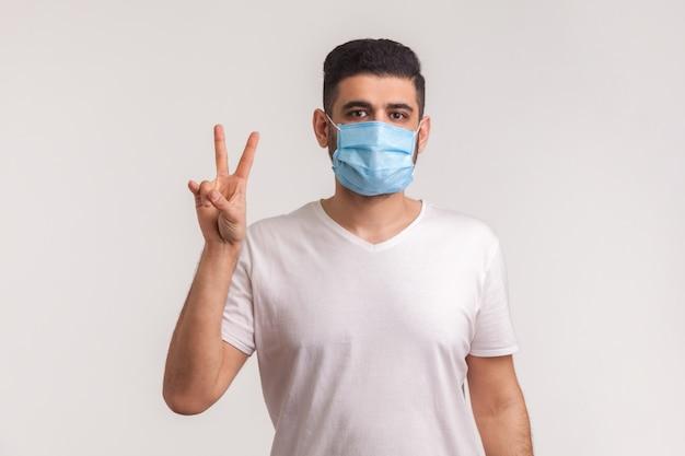 Mężczyzna w masce pokazujący gest zwycięstwa, radujący się wyzdrowienie z infekcji, choroby układu oddechowego