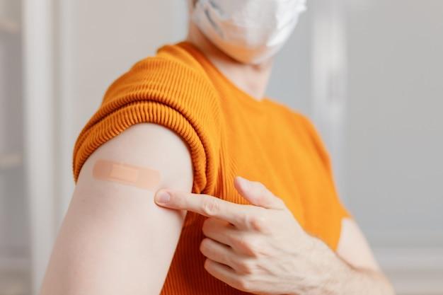 Mężczyzna w masce pokazujący ramię z bandażem po zaszczepieniu w ramach programu szczepień przeciwko covid-19.