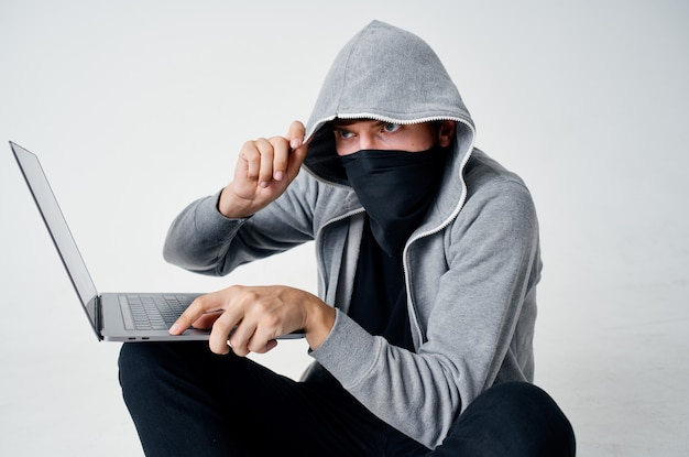Mężczyzna w masce siedzi na podłodze przed włamaniem do laptopa