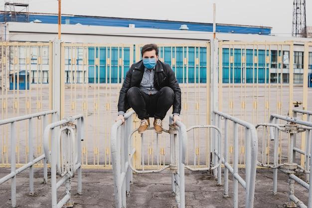 Mężczyzna w masce skacze przez płot, pojęcie uchodźcy, kwarantannę koronawirusa.