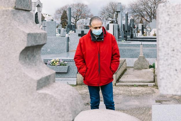 Mężczyzna w masce, smutny i modlący się, przed grobem zmarłego krewnego w czasach covid-19