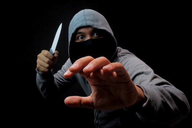 Mężczyzna w masce trzymający nóż w ciemności, zbrodnia przemocy lub ilustracja rabunku
