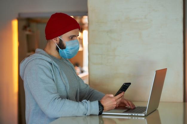 Mężczyzna w masce twarzy pracuje na swoim laptopie