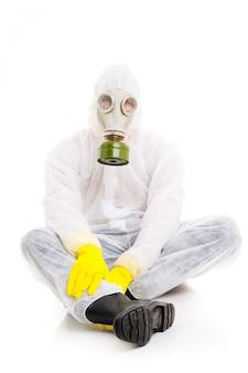 Mężczyzna w maski gazowej obsiadaniu na podłoga