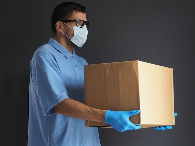 Mężczyzna w medycznej masce i rękawiczkach dostarczył paczkę. kurier z kartonowym pudełkiem. usługa dostarczania paczek podczas epidemicznego koronawirusa pandemicznego 2019-ncov, wirus covid-19.