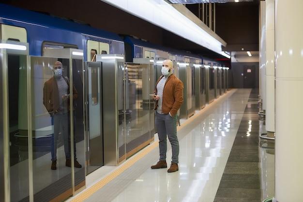 Mężczyzna w medycznej masce na twarz, aby uniknąć rozprzestrzeniania się koronawirusa, trzyma telefon komórkowy, czekając na pociąg w metrze