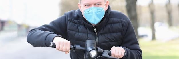 Mężczyzna w medycznej masce ochronnej jeździ skuterem elektrycznym po mieście