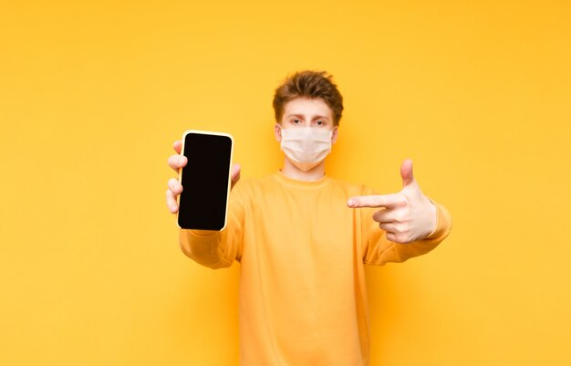 Mężczyzna w medycznej masce ochronnej na żółtym, trzyma smartfon z czarnym ekranem i wskazuje palcem. koronawirus pandemia.