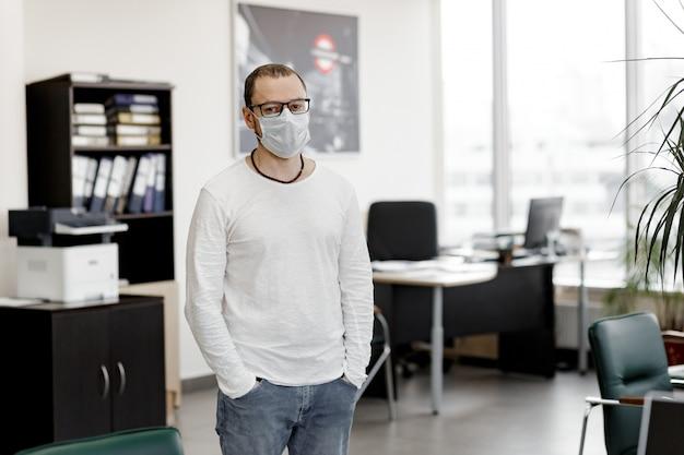 Mężczyzna w medycznej masce stoi przed pustym biurem.