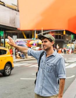 Mężczyzna w mieście próbuje zatrzymać taksówkę