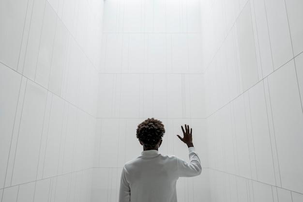 Mężczyzna w minimalistycznym białym wnętrzu inteligentnego domu