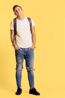Mężczyzna w modnych ubraniach z plecakiem w okularach w nowoczesnym stylu