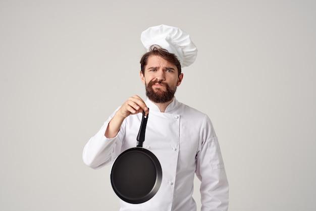 Mężczyzna w mundurze kucharza gotowania na jasnym tle kuchni