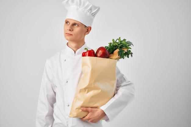 Mężczyzna w mundurze kucharza z paczką artykułów spożywczych dostarczanie usługi restauracyjnej