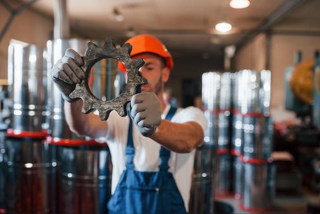 Mężczyzna w mundurze pracuje nad produkcją. nowoczesna technologia przemysłowa.