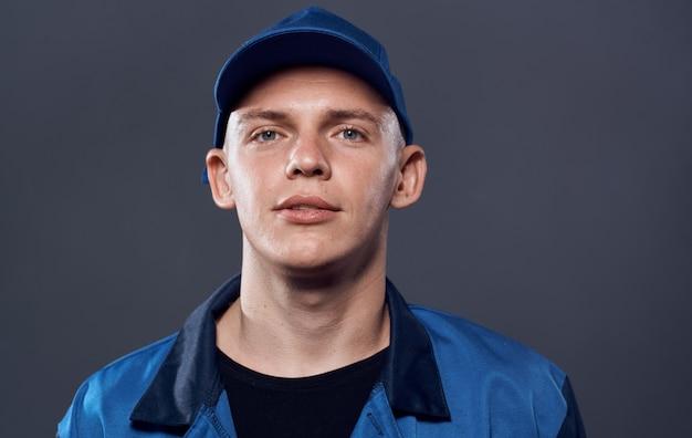 Mężczyzna w mundurze roboczym niebieska czapka przycięte widok usługi pracy. wysokiej jakości zdjęcie