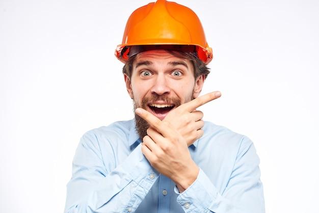 Mężczyzna w mundurze roboczym z pomarańczowym kask na białym tle