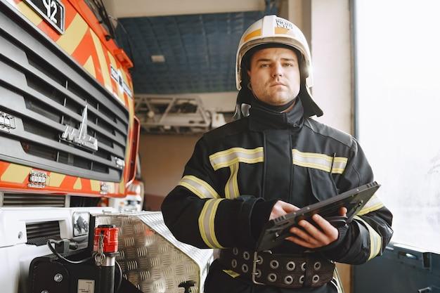 Mężczyzna w mundurze strażaka. strażak z tabletem. facet w pobliżu wozu strażackiego