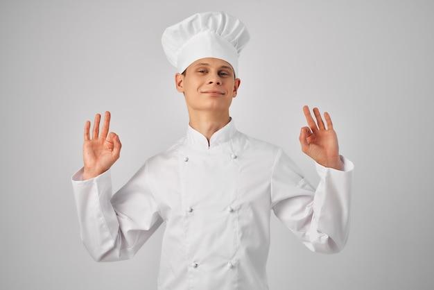 Mężczyzna w mundurze szefa kuchni gestykulujący ręką pracujący w restauracji profesjonalista