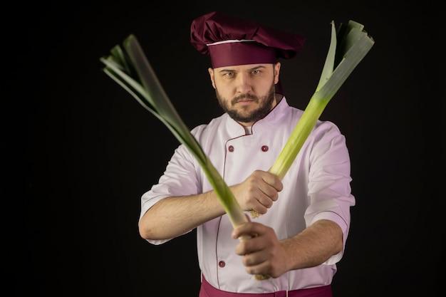 Mężczyzna w mundurze szefa kuchni trzyma dwie łodygi porów przecinające je jak broń