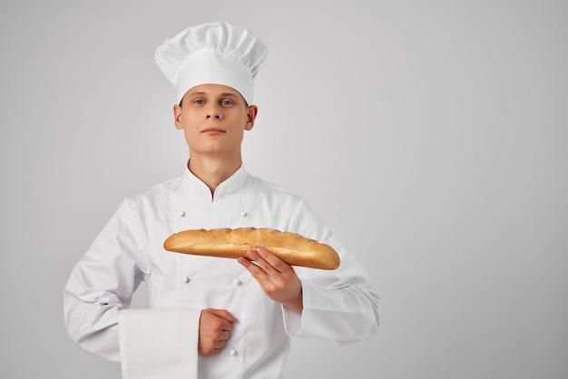 Mężczyzna w mundurze szefa kuchni trzymający robotę zawodową w piekarni bochenek