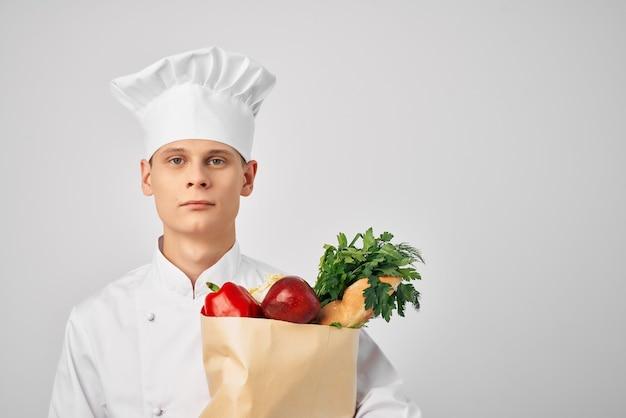 Mężczyzna w mundurze szefa kuchni z artykułami spożywczymi gotuje pracę w restauracji