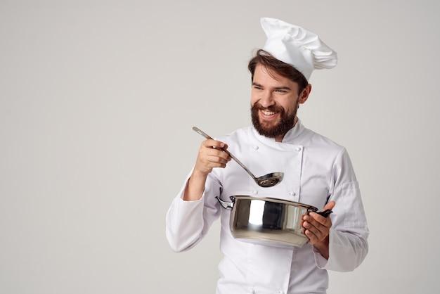 Mężczyzna w mundurze szefa kuchni z patelnią w rękach przygotowujący jedzenie na jasnym tle