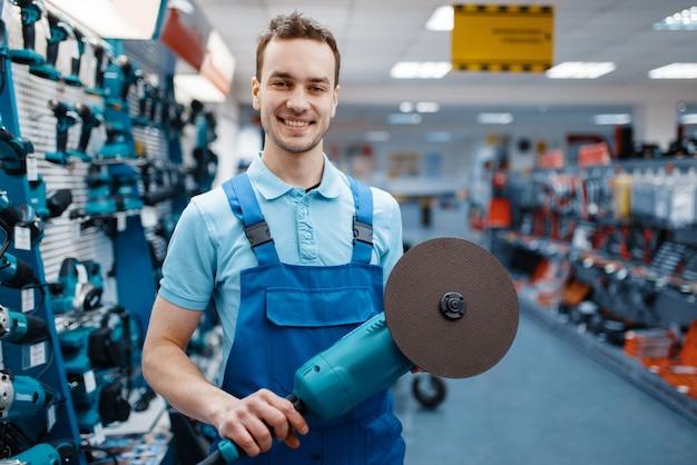Mężczyzna w mundurze trzyma szlifierkę kątową w sklepie z narzędziami