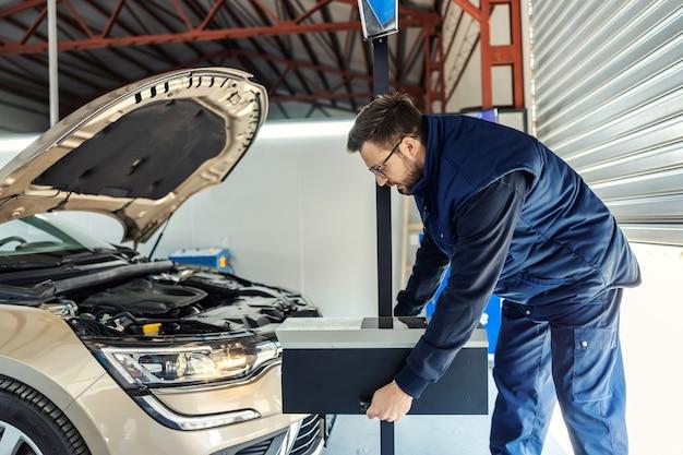 Mężczyzna w mundurze trzyma w ręku skrzynkę z narzędziami w warsztacie przed samochodem z otwartą maską