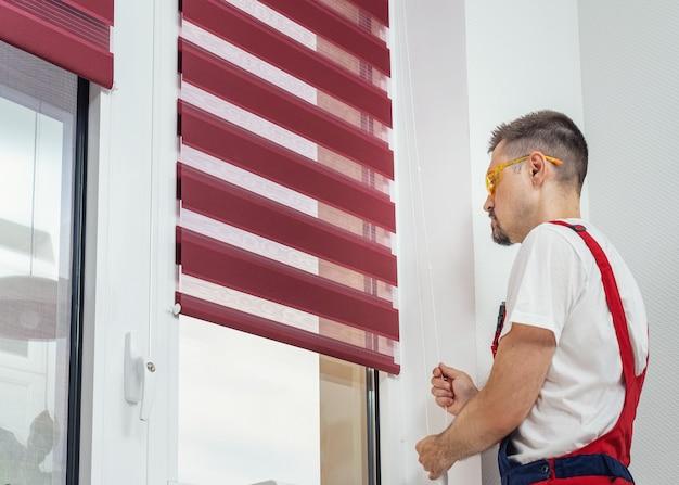Mężczyzna w mundurze zakładający nowe rolety okienne