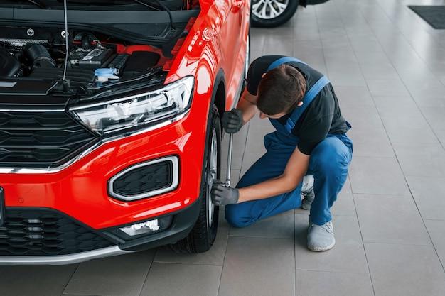 Mężczyzna w mundurze zmienia oponę samochodową. koncepcja serwisu samochodowego