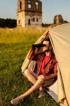 Mężczyzna w namiocie kempingowym patrząc przez lornetkę