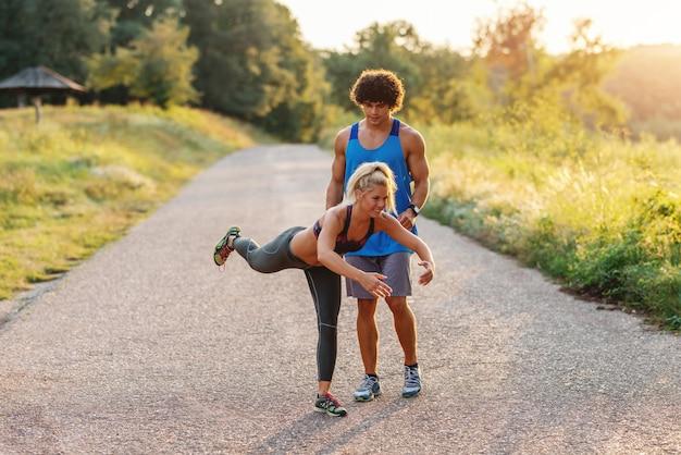 Mężczyzna w niebieską koszulkę, pomagając blond kobieta z koński ogon, aby zrobić ćwiczenia równowagi w przyrodzie. letni dzień. pełna długość.
