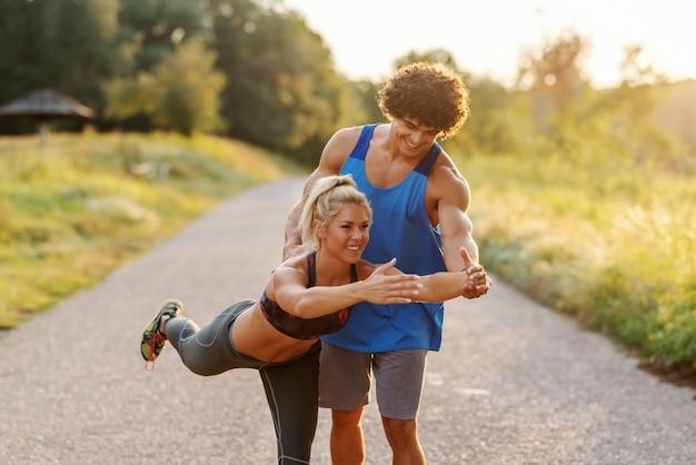 Mężczyzna w niebieską koszulkę, pomagając blond kobieta z koński ogon, aby zrobić ćwiczenia równowagi w przyrodzie. letni dzień. trzy czwarte długości.