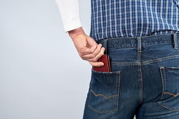Mężczyzna w niebieskich dżinsach i koszuli w kratę wsuwa skórzany brązowy portfel do tylnej kieszeni