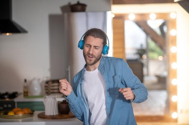 Mężczyzna w niebieskich słuchawkach słucha swojej ulubionej piosenki