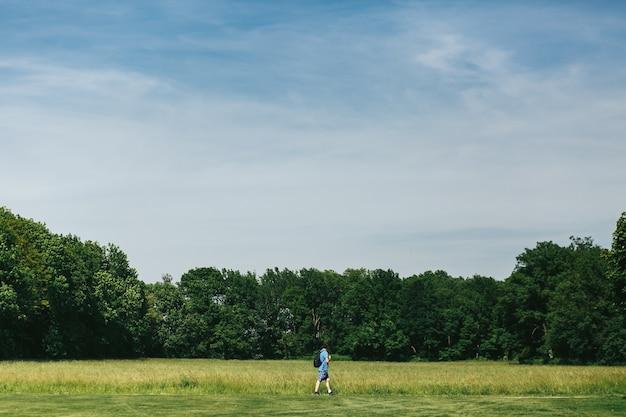 Mężczyzna w niebieskich szortach spaceruje po zielonym trawniku