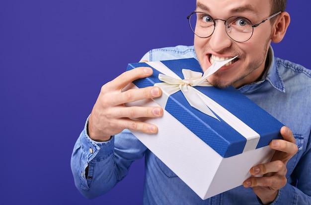 Mężczyzna w niebieskiej dżinsowej koszuli i okularach próbuje rozwiązać obecne zęby
