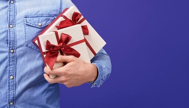 Mężczyzna w niebieskiej dżinsowej koszuli z dwoma prezentami z czerwoną czapką w dłoniach