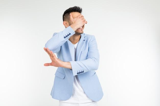 Mężczyzna w niebieskiej klasycznej kurtce zamyka rękę i prosi o usunięcie czegoś na białym tle