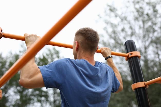 Mężczyzna w niebieskiej koszulce podciąga się na poziomym pasku w parku.