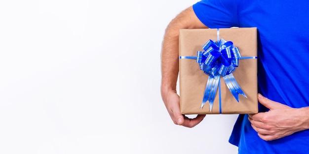 Mężczyzna w niebieskiej koszulce trzyma pudełko